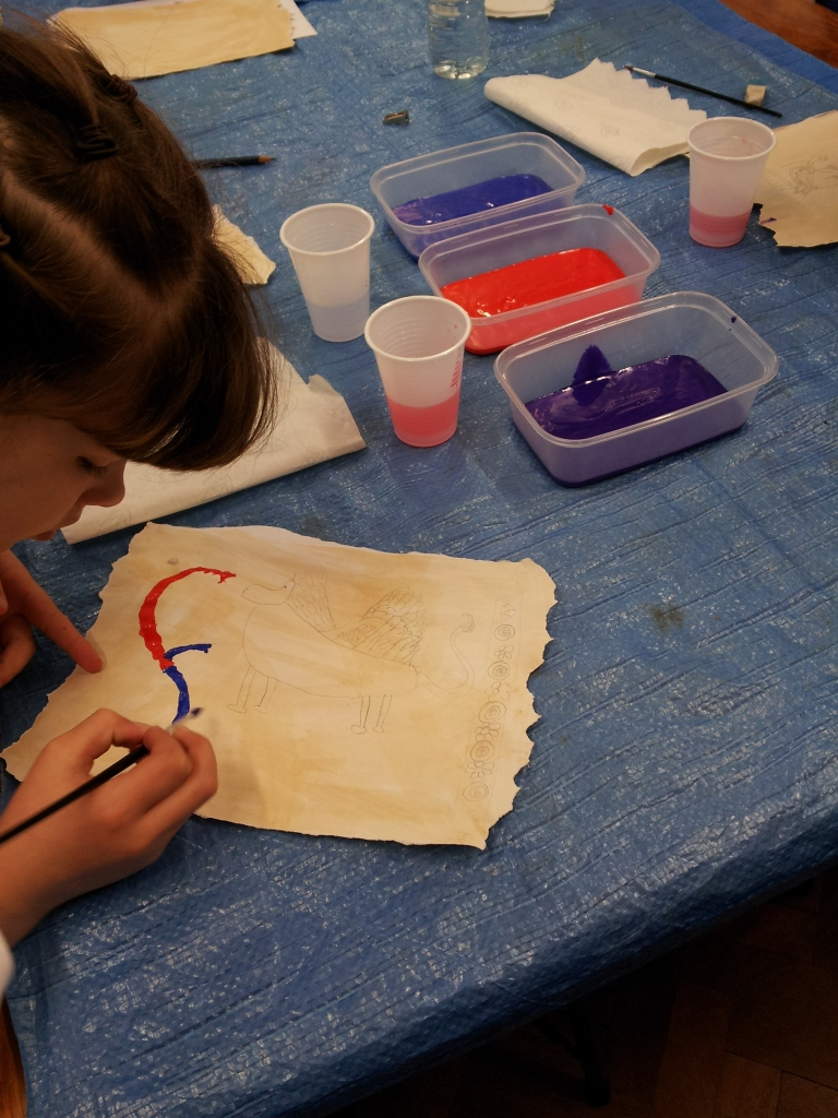 Child paining on paper to create an illuminated medieval manuscripts.