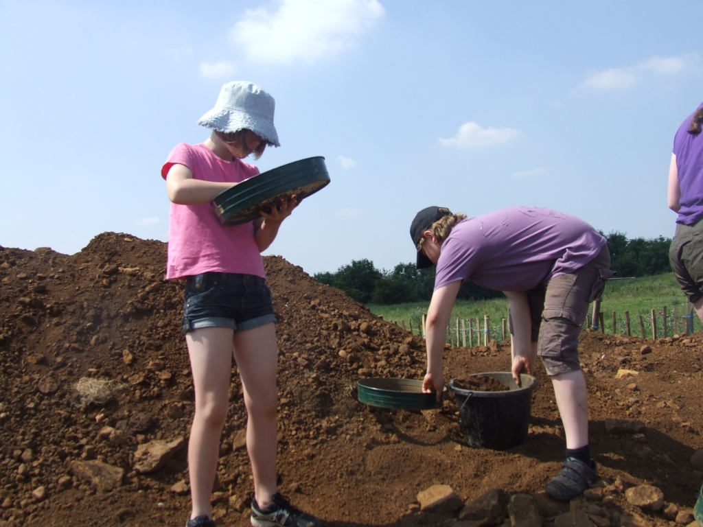 Children looking for artefacts whilst sieving soil on a spoil heap during an archaeological excavation at Burrough Hill Iron Age hill fort.