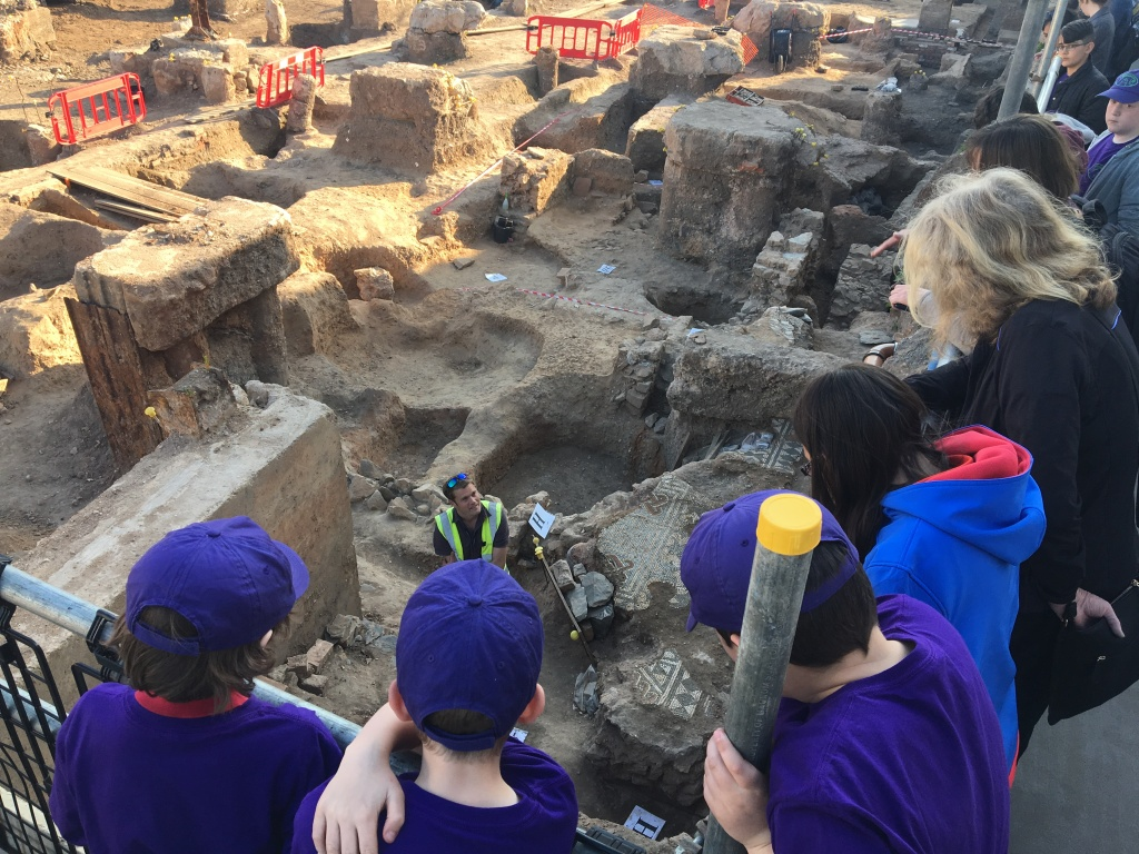 Children looking down from a viewing platform at a Roman mosaic as an archaeologists explains what they can see.