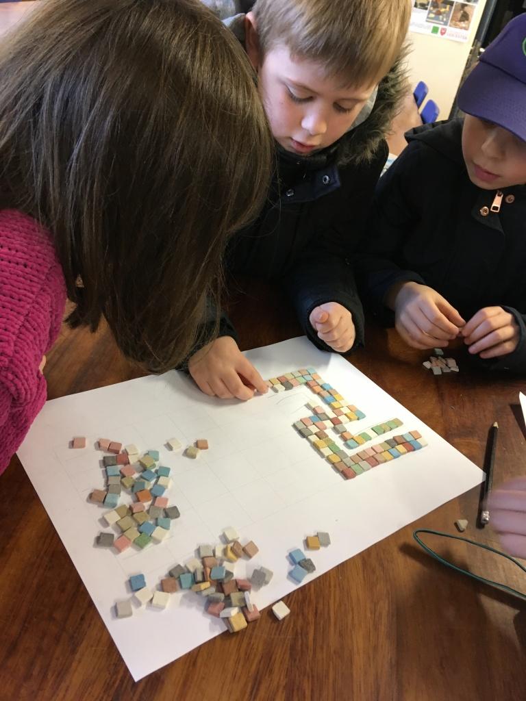 Children designing Roman mosaics with ceramic tiles.